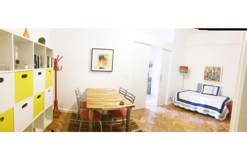 Sala de jantar com bi-cama e no fundo a porta de correr com acesso ao quarto