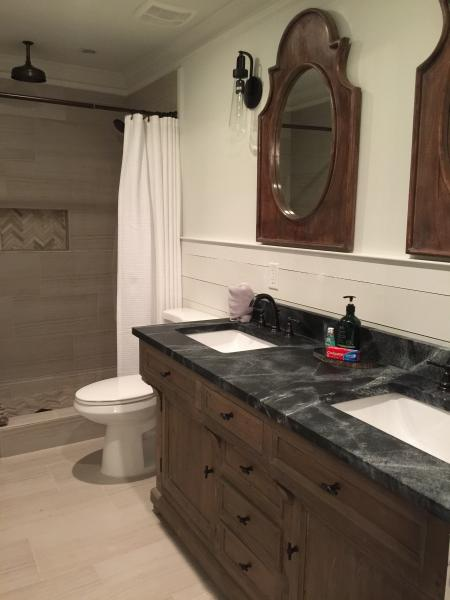 Master bathroom dual shower heads including hand held and rain head