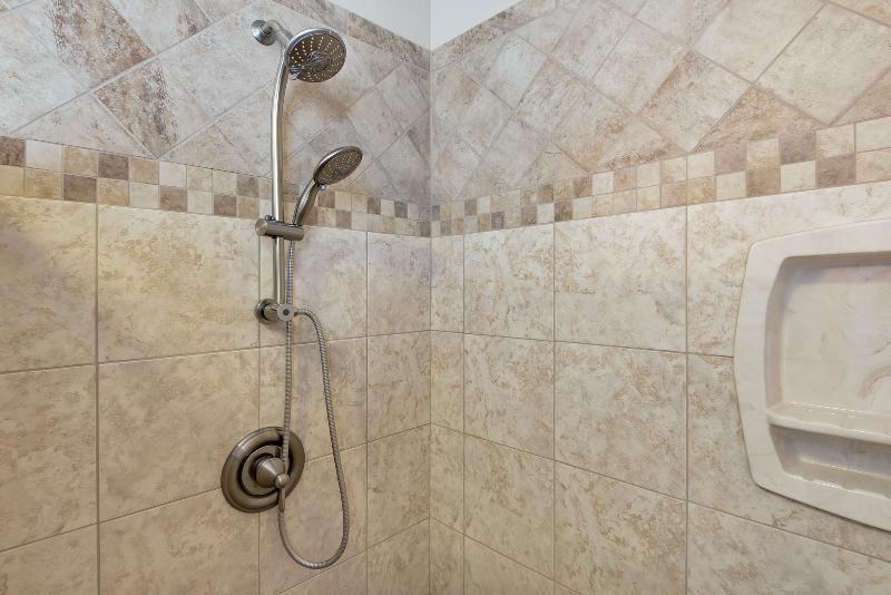 Huge walk-in master shower with double shower heads and corner bench