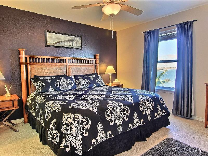 master bedroom with king bed, sitting area and beautiful view