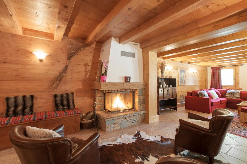 The living area is large and open plan, with two seating areas and cosy log fire.
