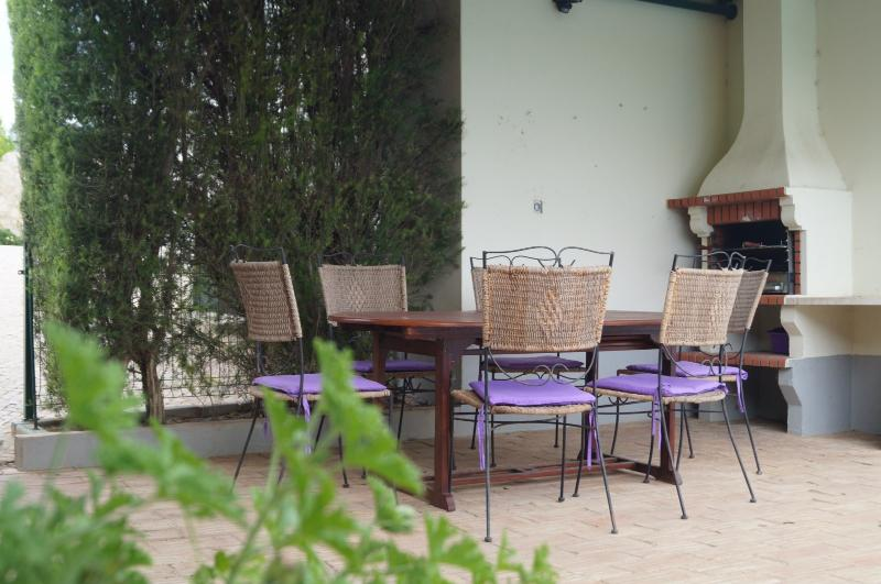 BBQ area, teak table and metal chairs