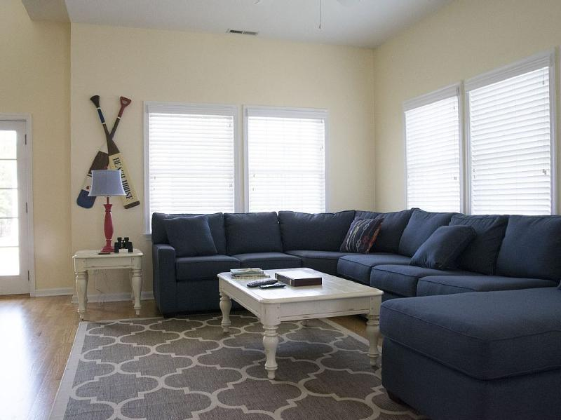 Open living room with new large sectional and lots of sunlight