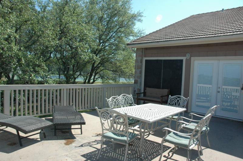 Upstairs balcony over looks tennis courts and lake