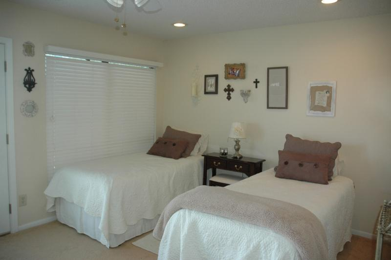 Vintage bedroom upstairs with two twin beds. Opens onto large balcony.
