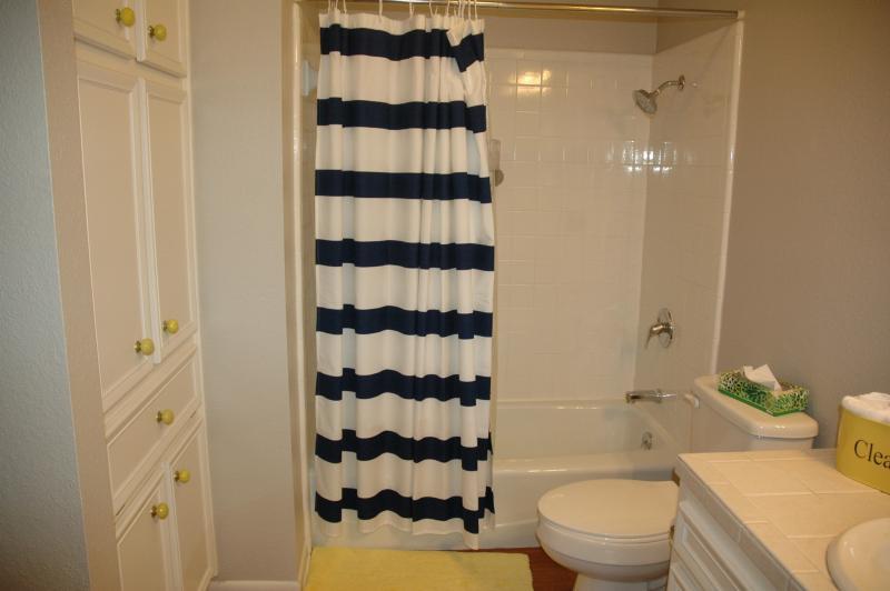 Bunk room bath has linen closet for more storage. Shampoo and shower gel dispenser in shower.