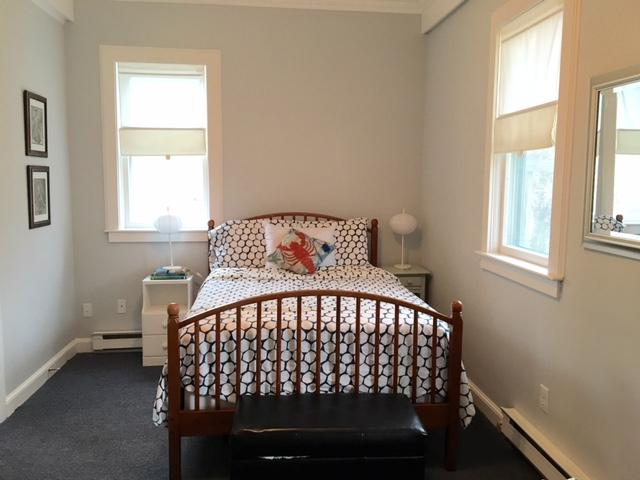 This bright and large first floor bedroom has a full size bed and chair for relaxing.