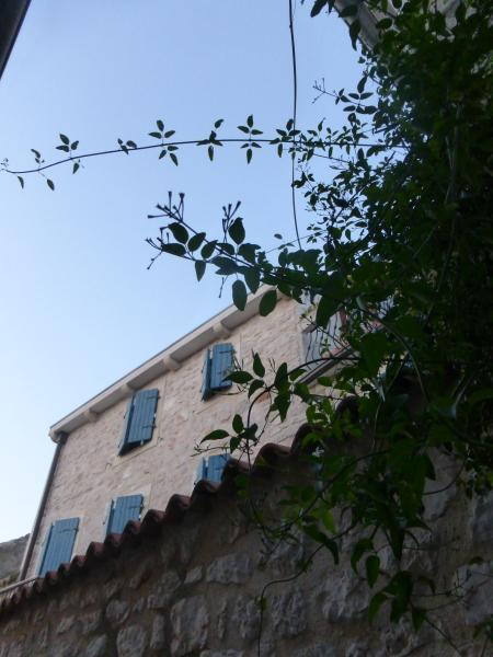 Vilmin Dvor is a charming, old 2-storey restored stone house. Street view behind tall private wall.