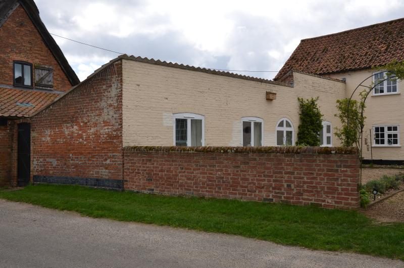 Front of cottage overlooks street and Staithe Farm garden. Over the road are Langley marshes.