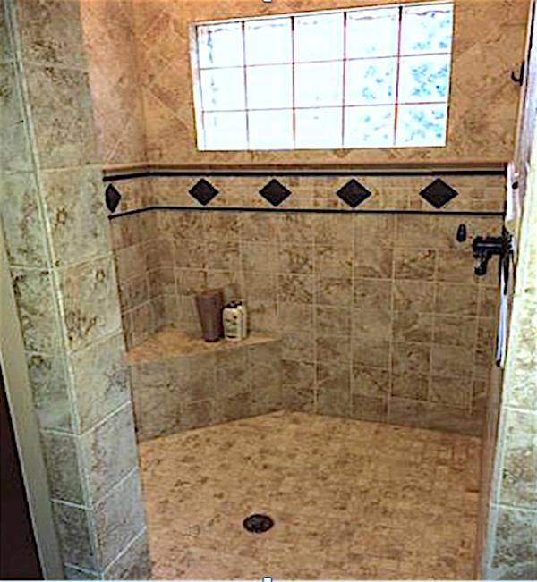 The large shower has dual shower heads and built-in seating