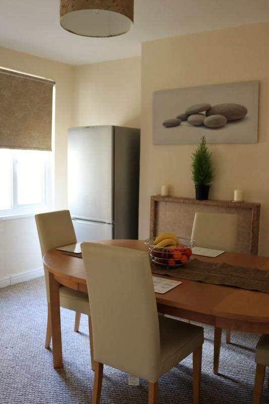 Dining room with fridge, dining table and chairs