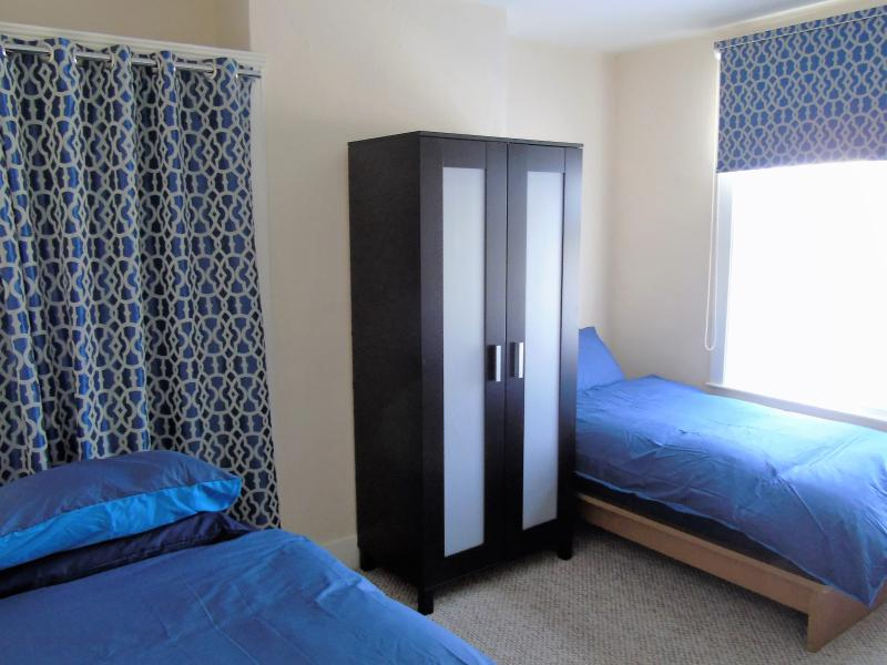 Bedroom 2 - consists of 3 single beds, wall mirror, wardrobe and extra space to hang clothes