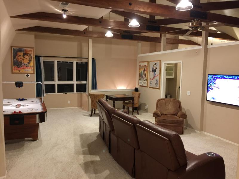 Large room w/open beam ceiling, theater seating, dining area, air hockey, lg. windows to enjoy views
