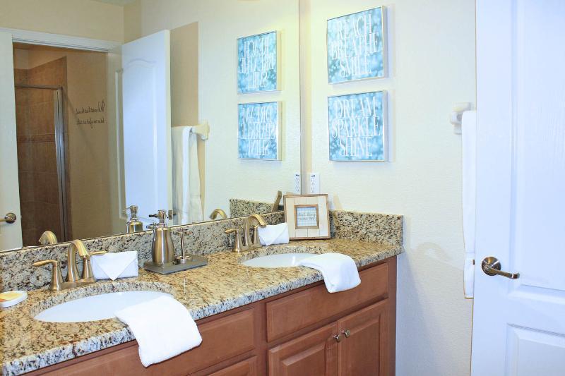 De gedeelde badkamer boven heeft 2 wastafels, krukje, föhn en toilet met een grote douche.