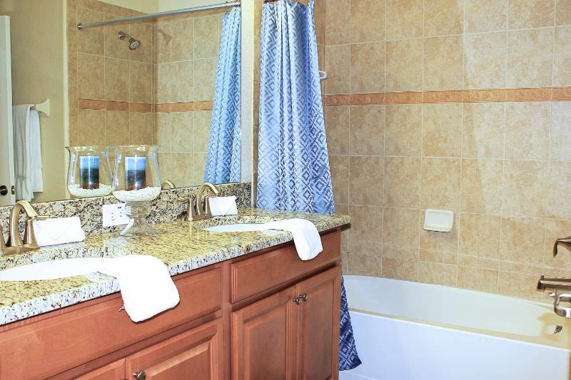 De ensuite badkamer heeft twee wastafels in een granieten aanrecht, bad / douche, een toilet, en föhn.