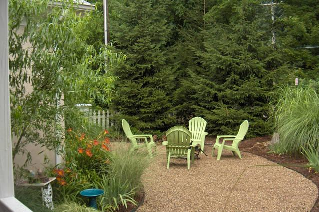 Front patio is nestled in pines and grasses for privacy.