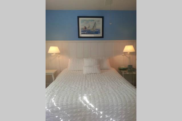 Queen size bed, white lap board paneling, shore blue walls make for a nautical master suite.