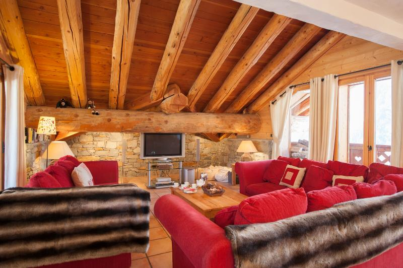The cosy living area with exposed wooden beams has balcony access, and plenty of comfortable seating