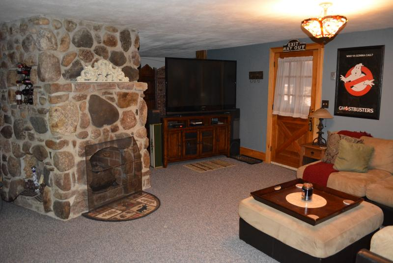Stone fireplace with big screen tv in basement.