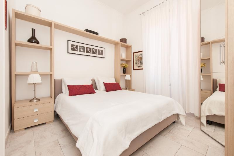 bedroom with queensize bed, closet space, drawers and tv