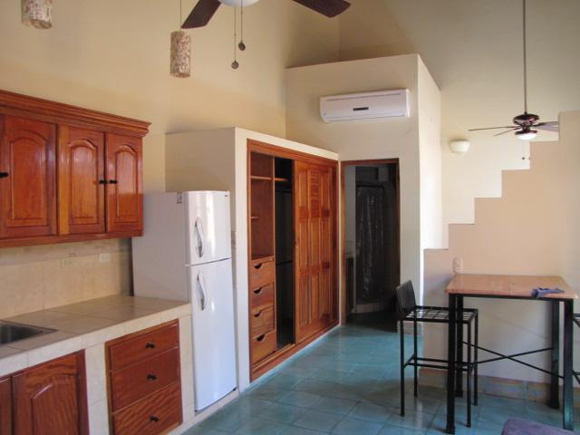 Studio with air conditioning, ceiling fans, full kitchen and privacy wall to separate the sleeping.