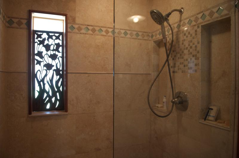 The tiled shower looks out into the woods, carvings from Bali adorn the cottage