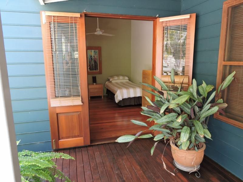 Third bedroom - two single beds, cedar french doors, ceiling fan, insect screens on windows
