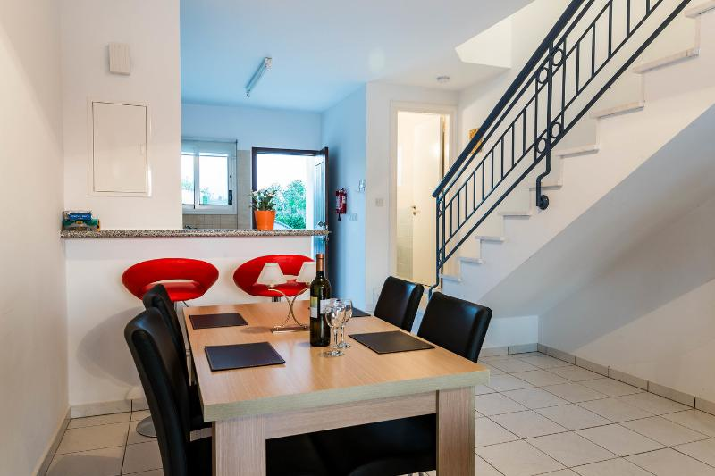 Dining Room with dining table, breakfast bar and marble staircase leading to bedrooms.