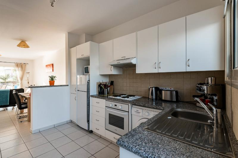Kitchen with oven, hobs, coffee machine, microwave and washing machine.