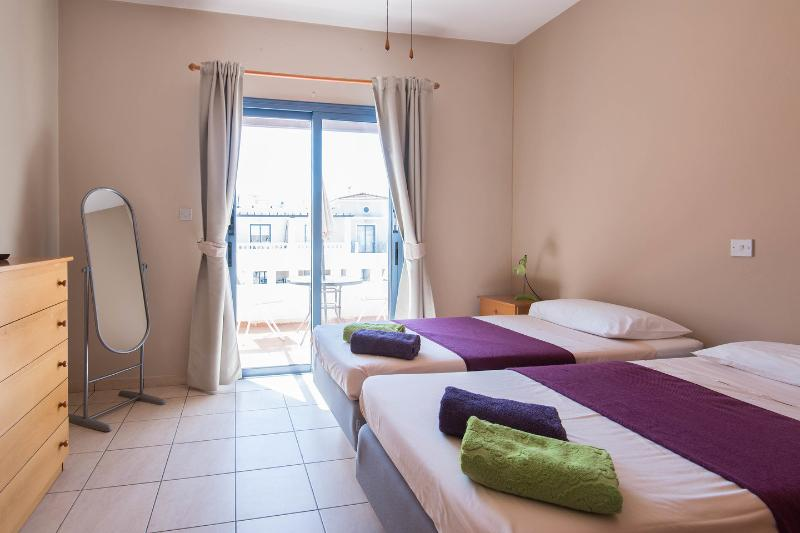 The Twin Bedroom: private balcony overlooking the pool area.