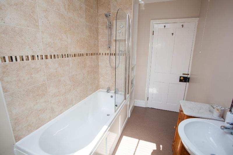 Bathroom - white sanitary ware including full size bath / shower, pedestal sink, toilet and cabinet.