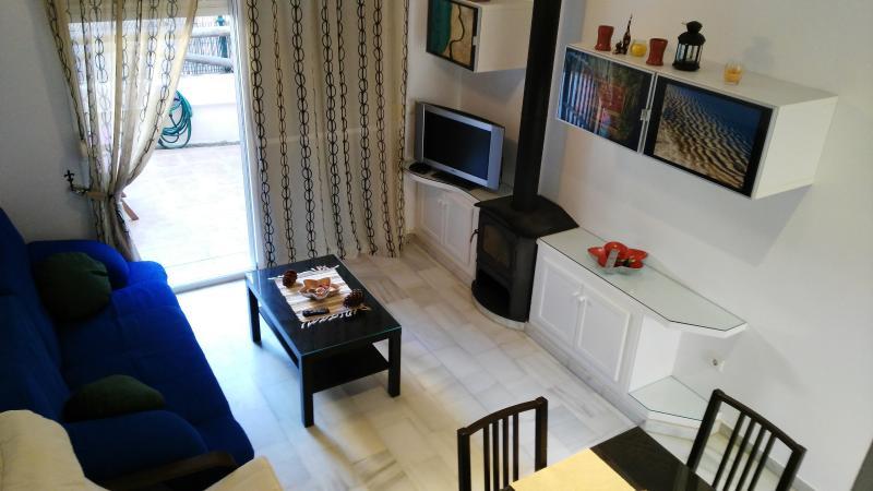 Salón con sofá cama, mesa comedor extensible y mesa baja. TV pantalla plana y amplio ventanal