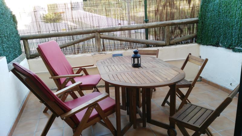 Amplia terraza con mesa, dos butacas y 6 sillas