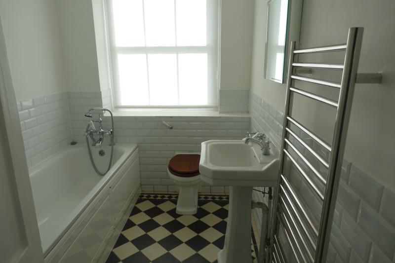 Badezimmer mit Badewanne, Dusche, Waschbecken mit Spiegel, beheizte Handtuchhalter und Fußbodenheizung.
