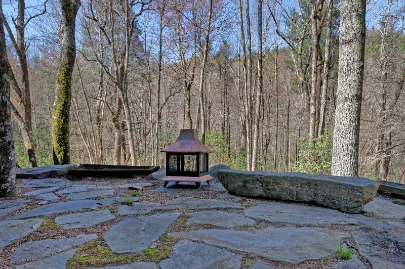 large stone patio overlooking the property downhill to stream