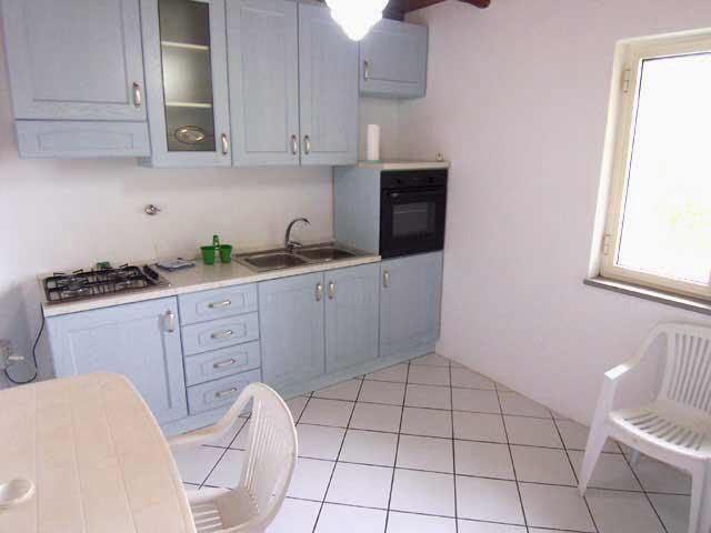 Kitchen 4 burner hob, oven, refrigerator, utensils and cutlery.