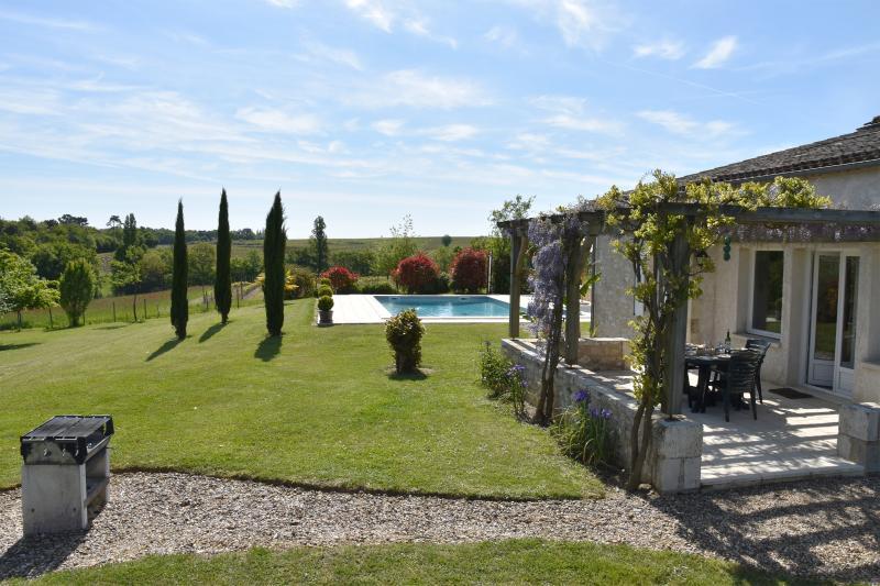 Outdoor-Essbereich mit Blick auf Garten und Pool.