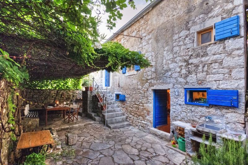 450 year-old house with vine-covered terrace, aluguéis de temporada em Stari Grad