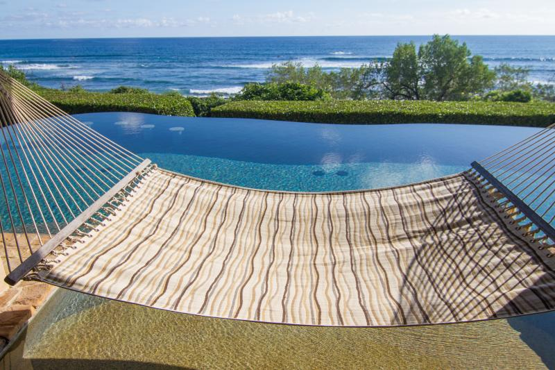 Hammock drapes lazily over beach entry of the pool