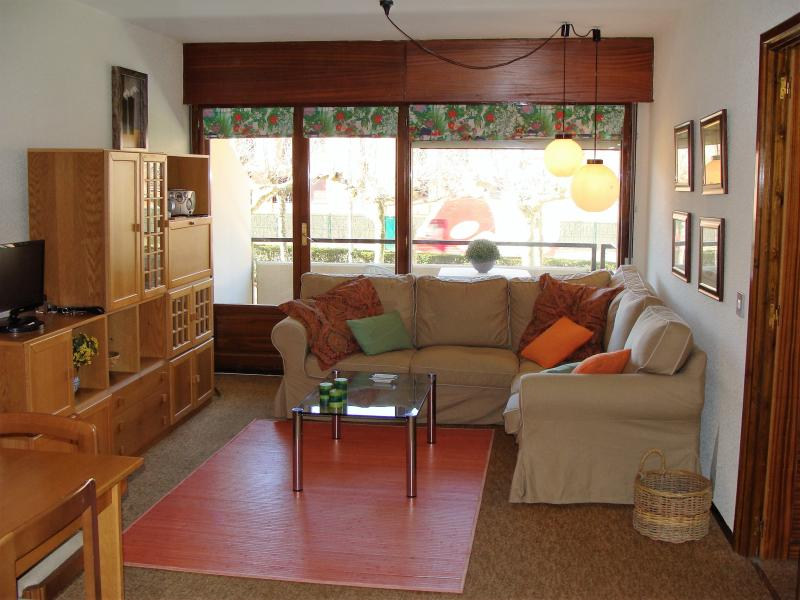 Salón comedor con amplio sofá y vistas al jardin