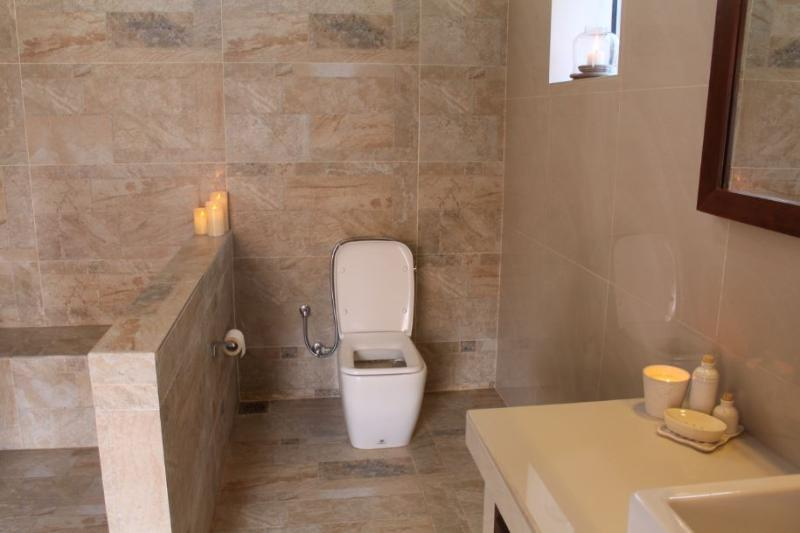 Spacious bathroom that lets in a lot of natural light. It comes with a rain shower and hot water.