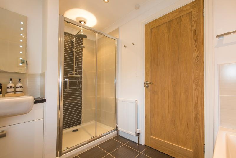 Modern bathroom with double ended bath and large shower cubicle.