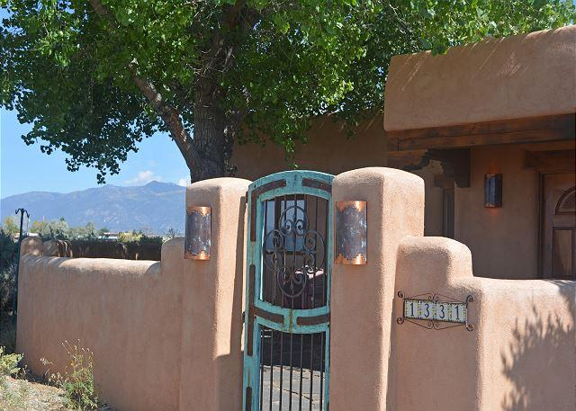 Turquoise gate entering adobe wall enclosed front courtyard