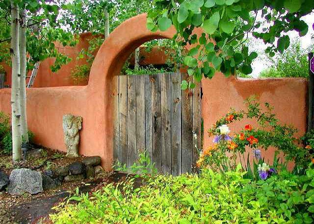 Romantic gardened entry with gated adobe archway