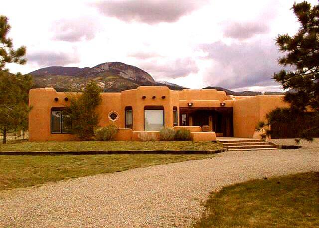 Exterior with mountain view background and short 15 minute drive to Taos Village, 35 ninute drive to Red River, NM