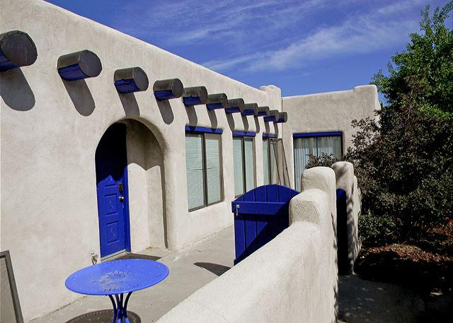 Front patio showing traditional 'Santa Fe' blue gate and door