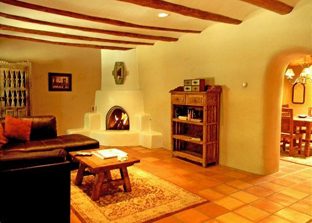 Inviting living room with fireplace and viga ceilings for authentic Taos southwest ambiance