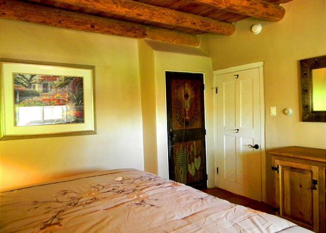 King bedroom boasts historic hand painted closet door and viga ceilings
