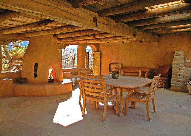 Extra large portal (covered patio in Spanish) with one of 5 kiva fireplaces, hot tub on lower terrace below