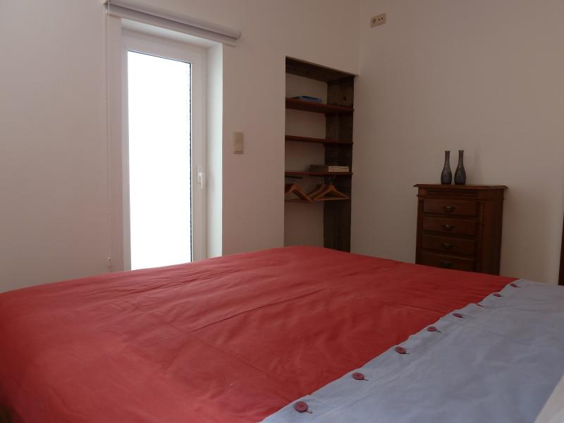 Chambre - armoire intégrée dans le mur de pierre et Camisole sur une commode